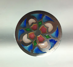 "Photo: Button #5 (round - approximately 1"" diameter) Fine silver, plique-a-jour enamel Completely handmade by Diane Echnoz Almeyda. $250. Plique-a-jour is considered the ""tour de force"" of enameling. It is the only enameling technique in which there is no metal backing behind the glass. It is, therefore, quite challenging. When light passes through the piece, it resembles miniature stained glass. In this example, fine silver sheet has been pierced and sawed. Ground glass has been melted in each cell. A circular shank has been soldered onto the reverse. Many firings are required to fill each cell. Enamels used in this button are semi-opaque, opalescent, and transparent."