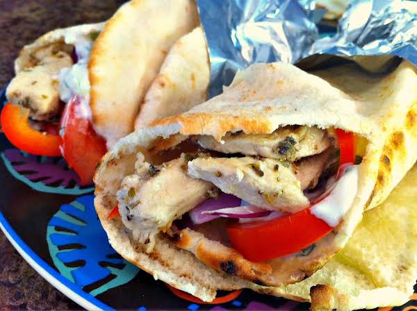 Two Gyros Filled With Chicken And Red Peppers On A Plate.