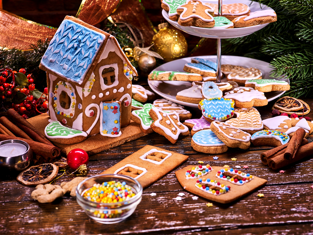 A gingerbread house project spread out on a table including a completed house and gingerbread cookies