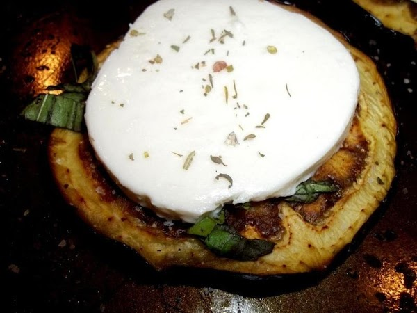 Add a slice of fresh cheese to each eggplant round. Sprinkle with Italian seasoning...