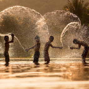 Splashing . by Visoot Uthairam - People Street & Candids ( mountain, silhouette, waterfall, thailand, little, travel, beauty, israel, people, kid, caucasian, child, girl, nature, cold, happy, family, woman, asia, wet, childhood, activity, water, spray, park, teen, grass, beautiful, togetherness, play, leisure, fun, young, enjoyment, vacation, splashing, sprinkler, outdoor, background, active, summer, healthy, day, view, garden, boy, outside )