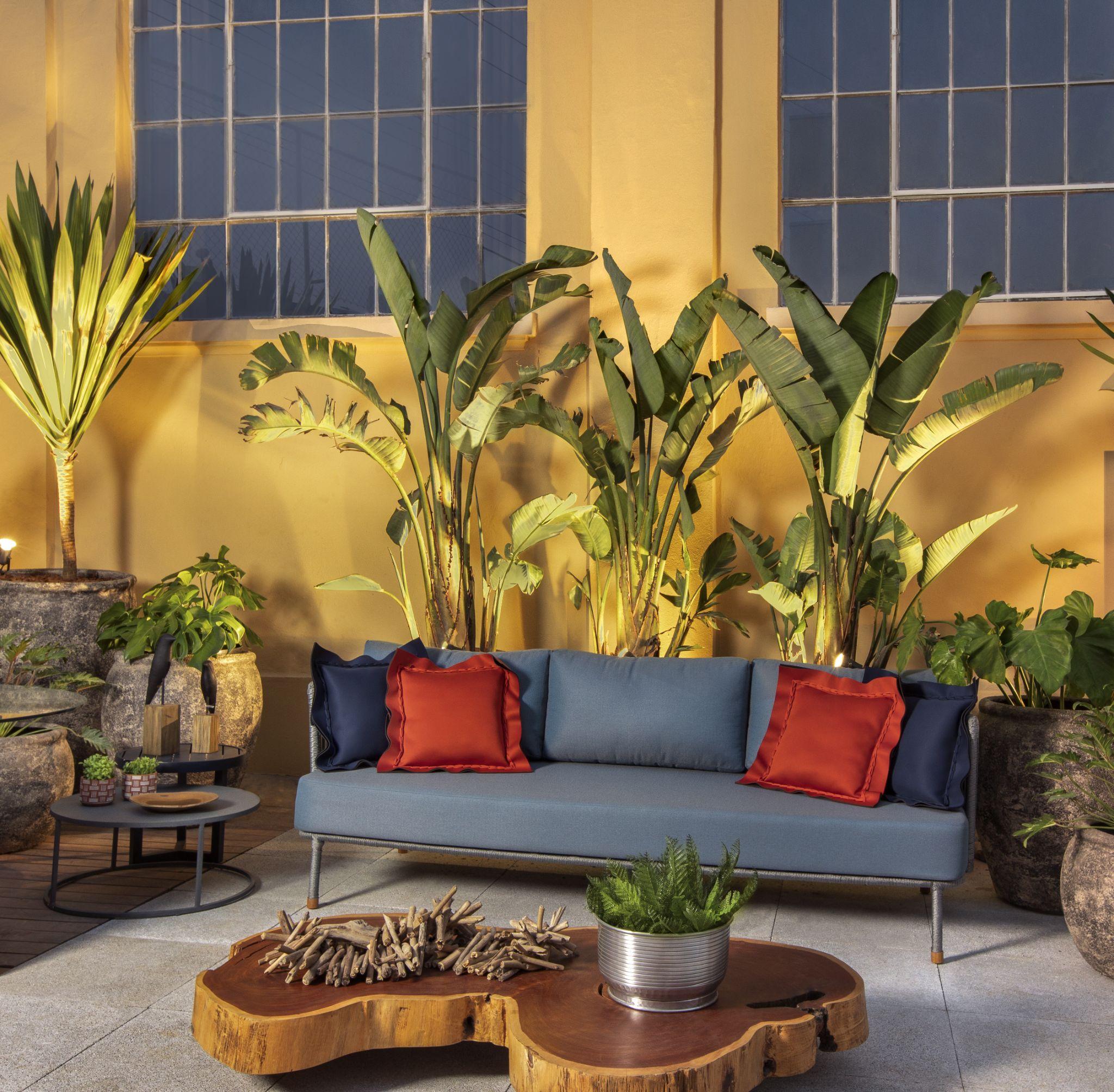 Lounge com sofá azul com almofadas azuis e vermelhas, piso drenante, plantas decorativas, mesinha de centro de madeira e parede amarela