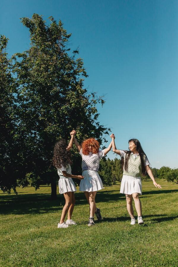 três amigas dançando na grama