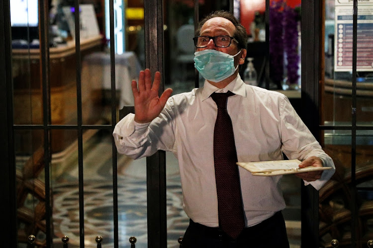 A waiter reacts as he prepares to close a bar in front of the Pantheon after the government introduced new restrictions to curb the coronavirus disease (COVID-19) infections in Rome, Italy, October 26, 2020.