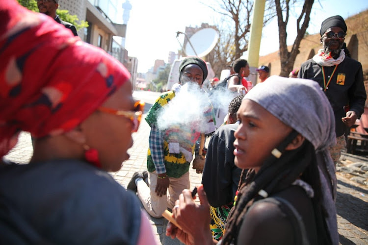 Members of the Rastafarian community smoke marijuana outside the Constitutional Court in Johannesburg. Picture: ALAISTER RUSSEL/ SUNDAY TIMES