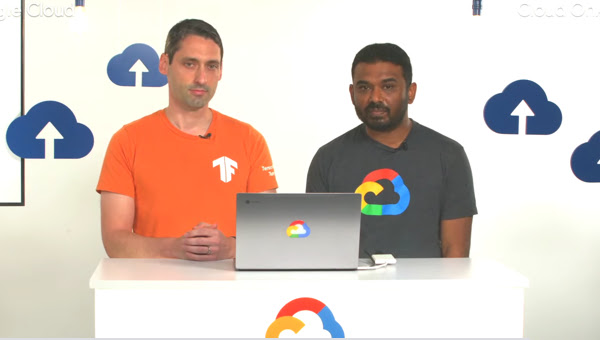 A man wearing a TensorFlow tee and a man wearing a Google Cloud tee sitting at a counter with a Google Cloud logo face front with a laptop between them