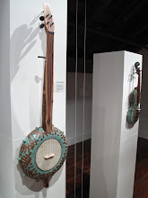 "Photo: Ceramic banjo and fiddle by Rob Mangum. Exhibition of ceramic musical instruments at The Bascom Arts Center in Highlands, NC. The exhibit, curated by Barry Hall and Brian Ransom, features musical instruments created by ceramic artists from around the world, as featured in the book ""From Mud to Music"" by Barry Hall."