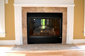 Photo: Porcelain Face with Diamond Hearth and Travertine Pebble Border with Wood Accent