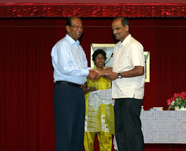 Photo: Prof. Bose giving the Excellence Award to Mr. Nambiar who received on behalf of his daughter Milashani, who is purshing degree in Applied Mathematics at University of California, Berlkey.