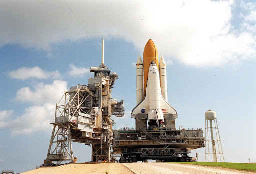Atop the mobile launcher platform Space Shuttle Atlantis arrives after rollout from the Vehicle Assembly Building.