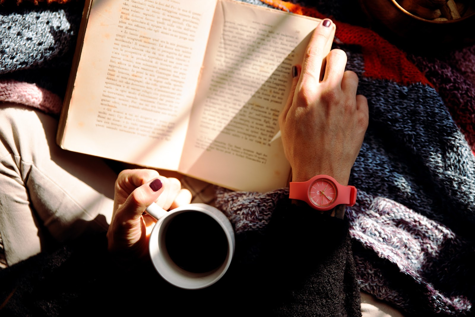 A person holds a cup of coffee while reading a book.