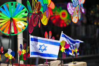 Photo: Two small Israel flags stands between colorful windmill toys in gift shop