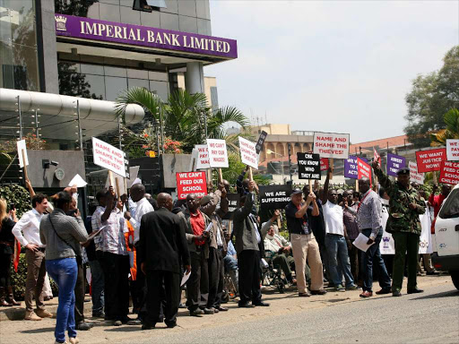 Imperial Bank depositors hold placards outside the Westlands branch during a past demonstration/FILE