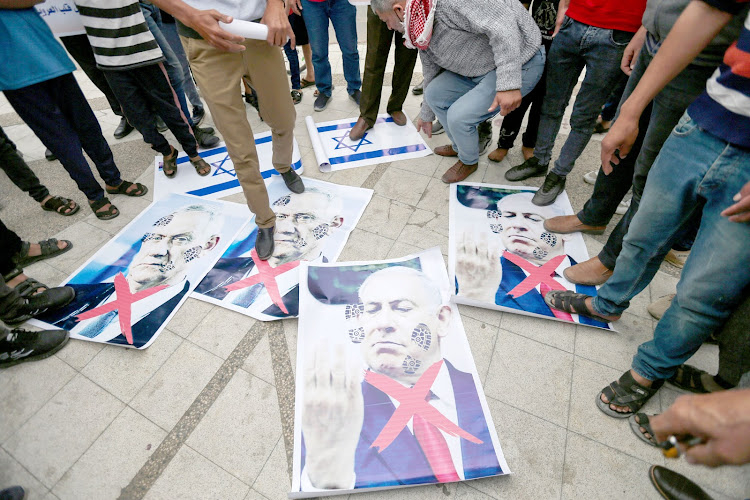 Palestinians step on posters depicting Israeli Defence minister Benny Gantz and Israeli Prime Minister Benjamin Netanyahu during an anti-Israel protest over tension in Jerusalem, in the southern Gaza Strip April 24, 2021.