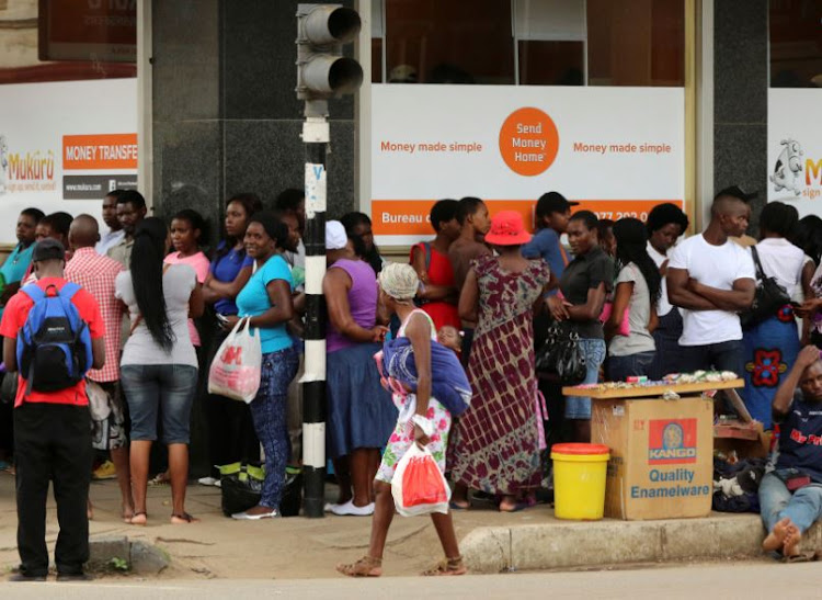 People queue to withdraw money from a bank in Harare.