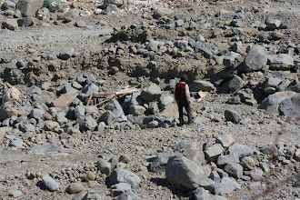 Photo: A man working on a shelter (house?) in the riverbed