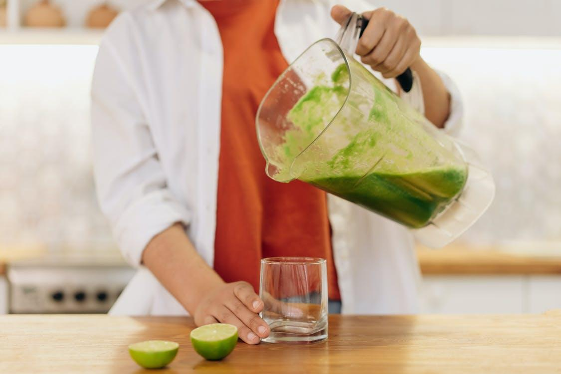 Person Pouring Fresh Smoothie In A Glass