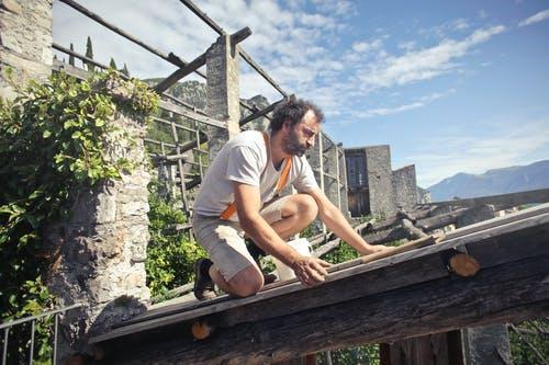 Focused man building roof of wooden construction