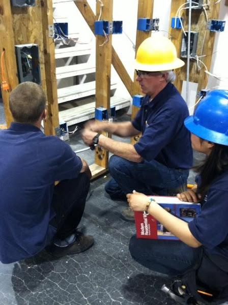 Photo: Building Trades teacher Tom Larsen helping Anna Sanchez and Sean Gates in residential wiring