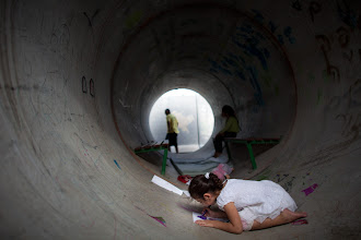 Photo: An Israeli child plays in a large concrete pipe used as a bomb shelter in Nitzan, Israel.