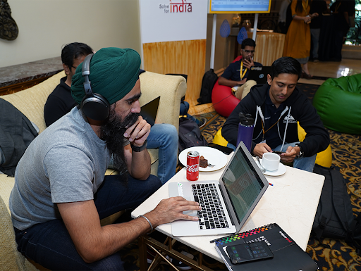 Man in green turban is wearing headphones and working on a laptop.