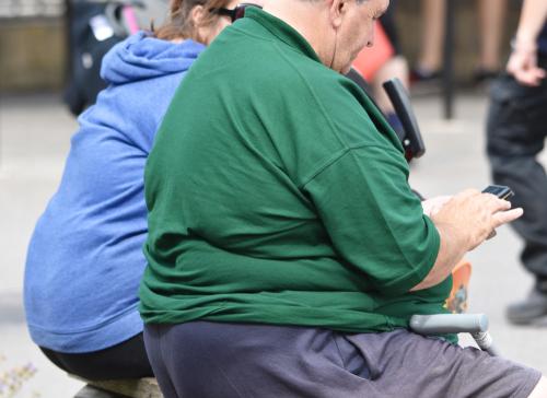 Homem obeso usando o celular