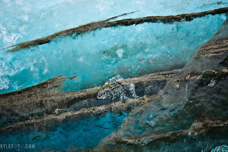 Photo: An iceberg's past Canadian Arctic From the photo of the day at http://www.kylefoto.com  The history of an iceberg is always etched into the ice. But rarely is hard evidence of it's birth so glaringly obvious the way it is in this detail shot of a piece of ice.  As I'm sure you've heard me say, an iceberg starts of as a glacier. A glacier starts off as layers of snow building up over hundreds or thousands of years along the mountain side. The tremendous weight of the snow on itself squeezes air out of the compacting ice and it becomes more clear and blue. So imagine a massive glacier slowly moving down a mountain side, the deepest part of the glacier is grinding away at the mountain, carving out U shaped valleys and pulverizing rock into dirt and silt. The ice at the bottom of the glacier is underneath hundreds of meters of ice, thus it's the clearest, but it will also be exposed to the rock and dirt. When the glacier finally dumps itself into the ocean these ancient pieces of ice will carry remnants of the mountain with it.  That's what you're looking at here. A piece of a glacier that was actively carving away at the mountain that has made it's way across the canadian arctic.  Photographic details: I had to poke my camera through a dark hole in an iceberg to get this, so it was relatively dark. I couldn't shoot like I normally do, I just stuck my arms out with my camera and hoped for the best. Yeah professional photographers blindly shoot and do guesswork too! I think I would have made it easier on myself if I used a higher ISO of 400 or so instead of 100.  1/50s f/5.6 ISO100 260mm