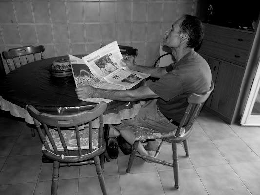 leggere un giornale in cucina. di Mario Romano
