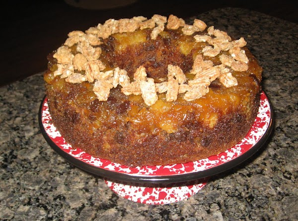 Just before serving, sprinkle half of pecans on top of cake. Slice cake and...
