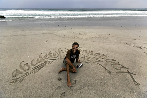 Beach life: Calligrapher Andrew van der Merwe on Witsands Beach, Cape Town. His work ranges from creating wine labels and designing logos to lettering scrolls. Picture: HALDEN KROG