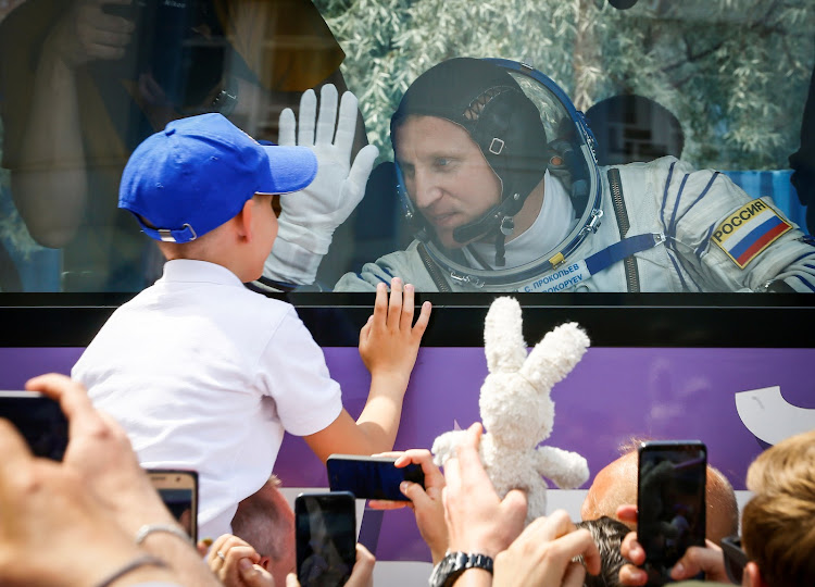 International Space Station crew member Sergey Prokopyev of Russia waves goodbye to his family from a bus shortly before leaving to board the spacecraft at the Baikonur Cosmodrome, Kazakhstan on Wednesday.
