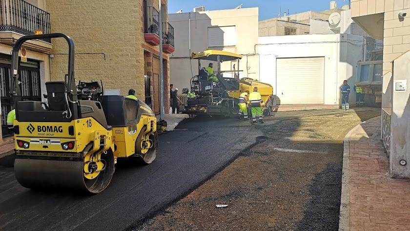 Los operarios asfaltando la vía de la calle Pozo.