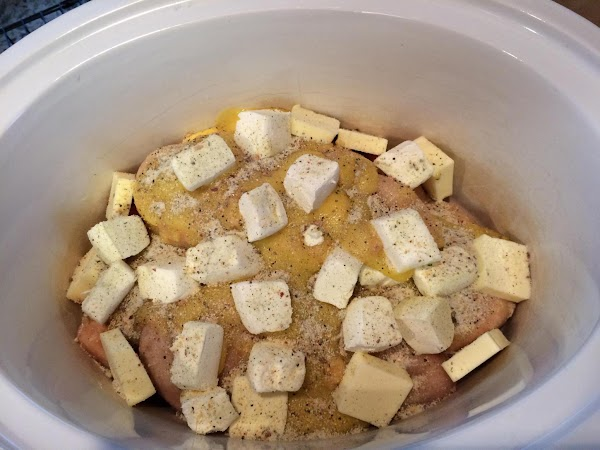 Place sliced, frozen chicken in the bottom of a crockpot. Cut butter and cream...