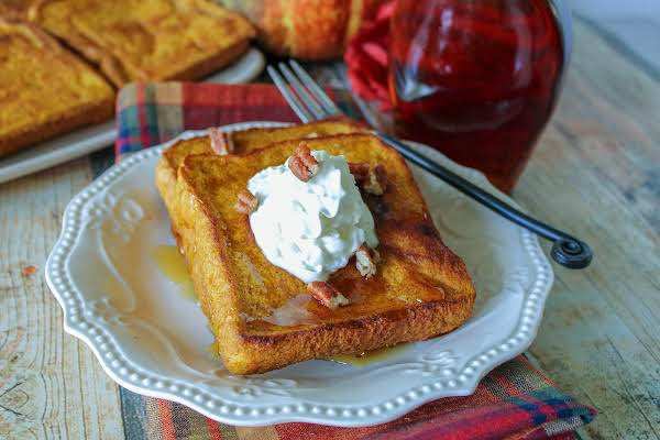 Baked Pumpkin Pie French Toast On A Plate With Syrup, Whipped Cream, And Nuts.