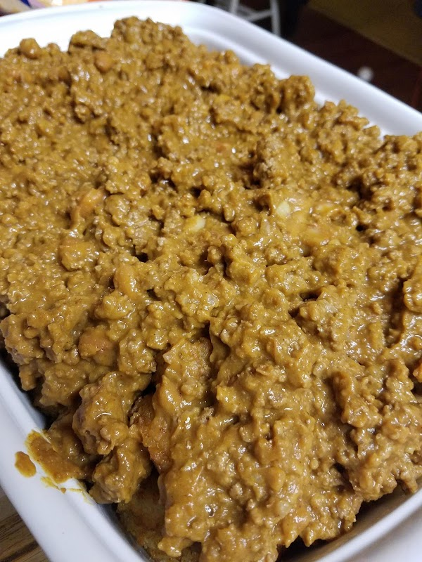 Spread meat and bean mixture coveringredients potato crisps. Cover with shredded cheese and sliced...