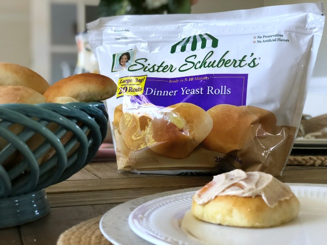 A bag of Sister Schubert\'s dinner rolls with a roll on a plate with butter on top of it.