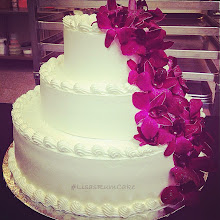 Photo: Floral wedding cake: smooth whipped cream frosting with fresh cascading orchids (provided by bride) and edible glitter.