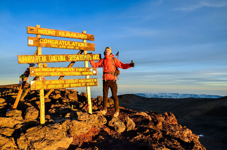 A hiker standing on Uhuru Peak, the summit of Kibo, one of the three volcanic cones of Mount Kilimanjaro.