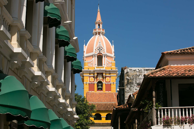 A cathedral's bell tower rises over a street in Old Cartagena, Colombia.