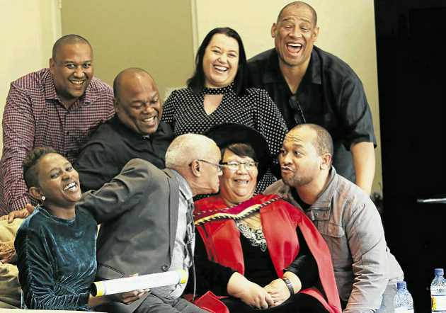 Family thronged around Daphne Murray, 72, who beamed with delight yesterday at the Abbotsford Christian Centre after being capped with a PhD by the University of Fort Hare. The party included (clockwise, from back left) two sons Tim and Manwell Wilson, her daughter-in-law Char nnee Wilson, two more sons Alliston and Ricardo Wilson, her husband William Murray and her daughter Amanda Wilson