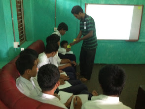 "Photo: Shrijan handing out sticky notes to the students. We asked them to write a sentence on the prompt ""What does Peace mean to you?"""