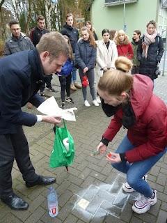Vorn putzt Schülerin, Bürgermeister assistiert, im Hintergrund Schülerinnen und Schüler.