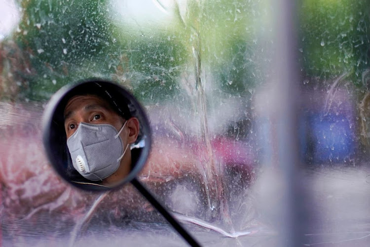 A man wearing a face mask is seen reflected in his electric bike's rearview mirror after the lockdown was lifted in Wuhan, capital of Hubei province and China's epicentre of the Covid-19 outbreak, on April 14 2020.