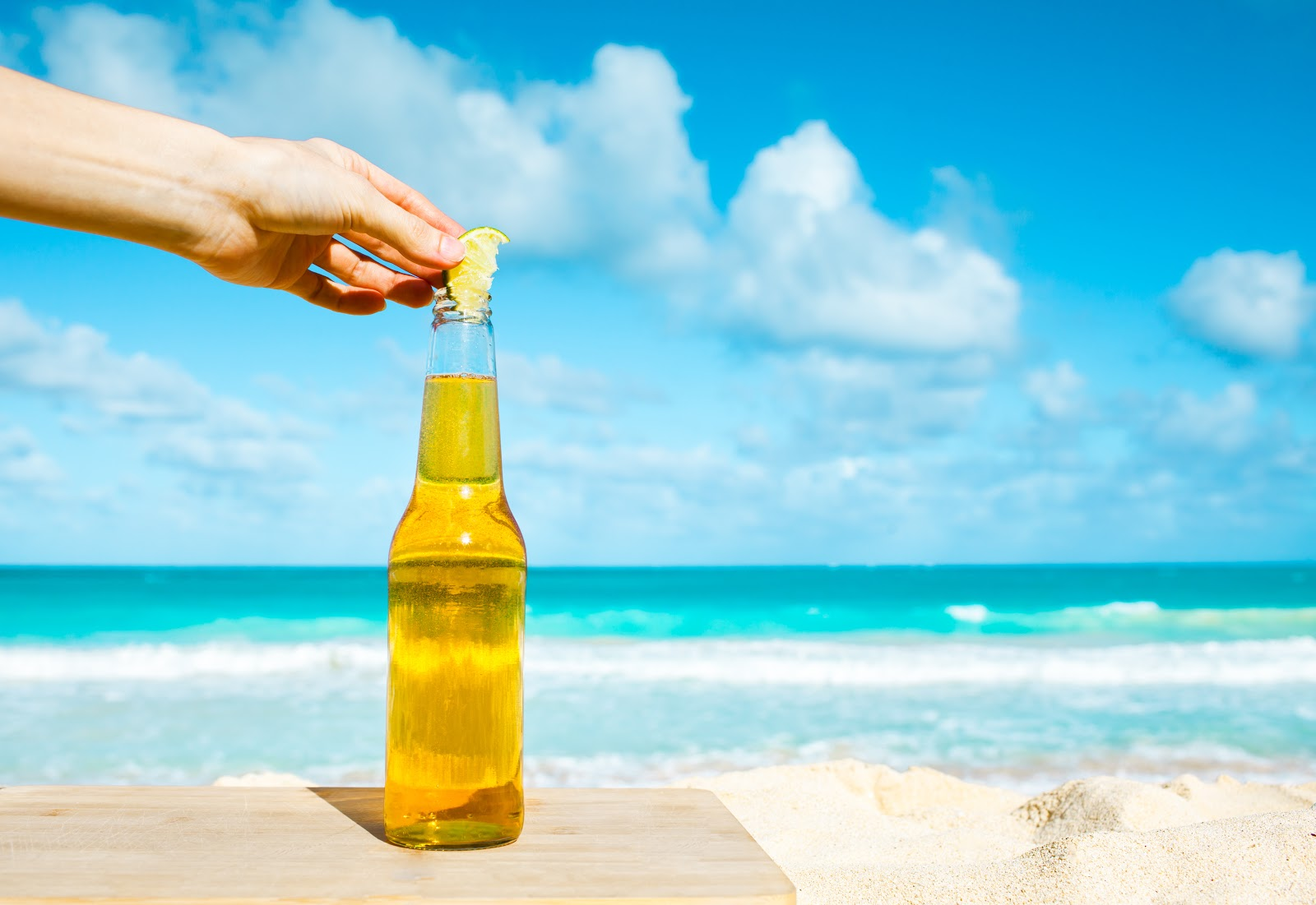 An image of a person placing a lemon into a beer bottle on a beach, emblematic of the Spanish lifestyle.