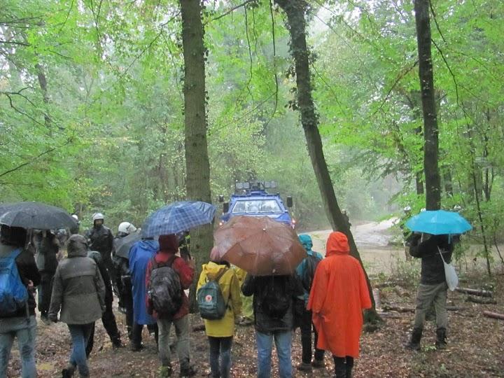 Waldspaziergänger im Regen, hinten Polizei.