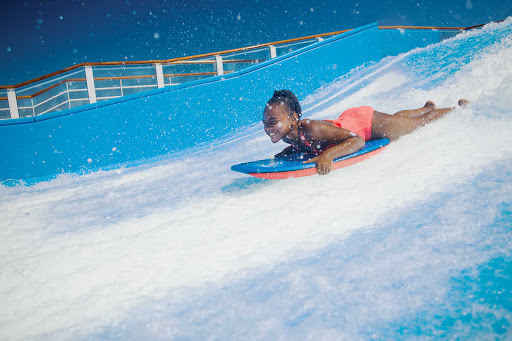 Harmony-of-the-Seas-flowrider-girl-slides.jpg - Grab a boogie board and tackle FlowRider on Harmony of the Seas.