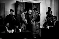 mannelijke gevangene met 2 agenten komen een ruimte met bureau's binnen