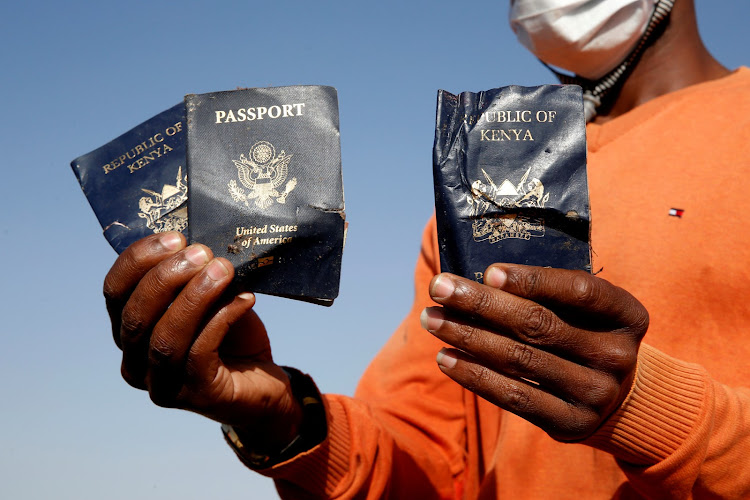 Man holds passengers' passports (two Kenyan and one American) found at the scene of the Ethiopian Airlines Flight ET 302 plane crash, near the town of Bishoftu, near Addis Ababa.