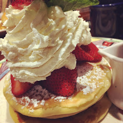 Gluten free pancakes topped with fresh strawberries and homemade whipped cream