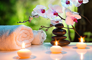 3 lit white tealights in front of two white towels, zen stones and a blooming orchid.